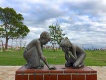 Imagen de una estatua de bronce de un muchacho y de una muchacha que juegan con mármoles en el parque de Meriken, Kobe imagen de archivo