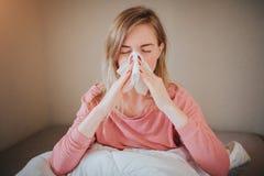 Imagen de una mujer joven con el pañuelo La muchacha enferma tiene mocos El modelo femenino hace una curación para el frío común Fotografía de archivo