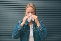 Imagen de una mujer joven con el pañuelo El modelo femenino enfermo tiene mocos Imagenes de archivo
