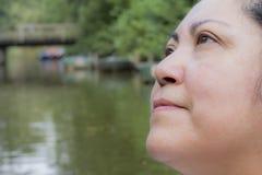 Imagen de una mujer pensativa que mira para arriba al cielo con una expresión de la felicidad imagenes de archivo