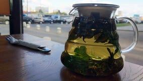 Imagen de una tetera en una tabla del café foto de archivo