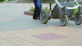 Imagen de vídeo de un hombre irreconocible con un cochecito de niño que camina abajo de la calle El padre feliz camina con un niñ metrajes