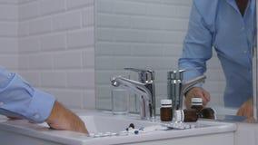 Imagen decepcionada de la persona en el cuarto de baño que toma píldoras y las drogas imagenes de archivo