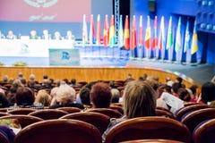 Imagen Defocused Gente en el auditorio Conferencia Internacional Banderas de los países diferentes en etapa foto de archivo libre de regalías