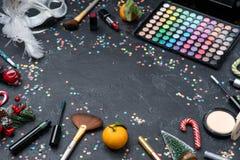 Imagen del árbol de navidad, mandarín, cepillos, barra de labios, paleta con las sombras en la tabla negra fotos de archivo