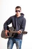 Imagen del adolescente en ropa, la sudadera con capucha y gafas de sol negras que es Imagen de archivo