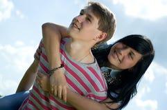 Imagen del adolescente y de la muchacha que abrazan sobre el cielo Imagen de archivo libre de regalías