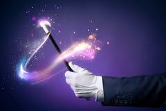 Imagen del alto contraste de la mano del mago con la vara mágica Imagen de archivo