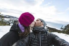 Imagen del amor joven de los pares felices divirtiéndose en montañas nevosas Imagen de archivo