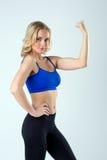 Imagen del atleta de sexo femenino atractivo que muestra el bíceps Imágenes de archivo libres de regalías