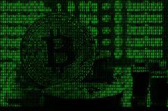 Imagen del código binario de los dígitos verdes claros, a través de los cuales la imagen del bitcoin físico Fotografía de archivo