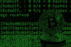 Imagen del código binario de los dígitos verdes claros, a través de los cuales la imagen del bitcoin físico Foto de archivo libre de regalías