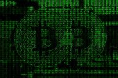 Imagen del código binario de los dígitos verdes claros, a través de los cuales la imagen del bitcoin físico Fotos de archivo libres de regalías