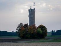 Imagen del chminey grande con los anntenas rodeados por los árboles coloridos del otoño foto de archivo libre de regalías
