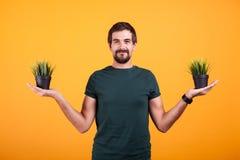 Imagen del concepto de la tranquilidad del hombre relajado que sostiene dos potes de hierba fotografía de archivo libre de regalías