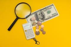 Imagen del concepto de un billete de banco de 100 dólares, de la lupa, de una calculadora y de la moneda en un fondo amarillo fotos de archivo libres de regalías