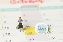Imagen del concepto de un calendario Tiro del primer de una chincheta atada La cena de las palabras escrita en un cuaderno blanco foto de archivo