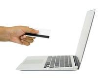 Imagen del concepto del comercio electrónico una mano con la tarjeta y el cuaderno de crédito Fotos de archivo libres de regalías