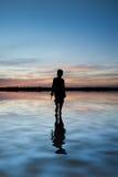 Imagen del concepto del muchacho joven que camina en el agua en paisaje de la puesta del sol Imagenes de archivo