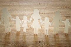 imagen del concepto del recorte de la cadena del papel de la familia que lleva a cabo las manos, sobre la tabla de madera fotos de archivo libres de regalías