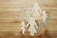 imagen del concepto del recorte de la cadena del papel de la familia que lleva a cabo las manos, sobre la tabla de madera imagen de archivo libre de regalías