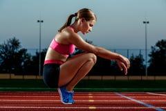Imagen del corredor o del esprinter de sexo femenino europeo joven hermoso que se sienta en pista al aire libre del estadio, sint Imagenes de archivo