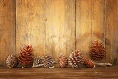 Imagen del día de fiesta con los conos del pino de la Navidad sobre fondo de madera Foto de archivo