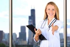 Imagen del doctor hermoso de la mujer que mira la cámara y que da una mano foto de archivo libre de regalías