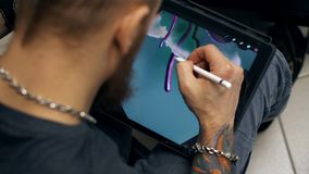 Imagen del drenaje del individuo en la tableta El diseñador trabaja en la tableta gráfica en la PC