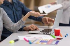 Imagen del equipo joven del negocio que discute proyecto en el ordenador imágenes de archivo libres de regalías