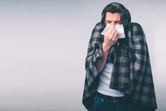 Imagen del estudio de un hombre joven con el pañuelo El individuo enfermo aislado tiene mocos el hombre hace una curación para el Fotos de archivo