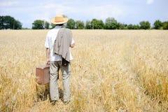 Imagen del hombre con la maleta en el campo de trigo encendido Imagen de archivo libre de regalías