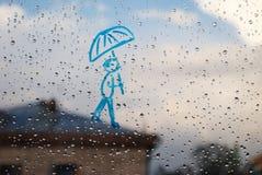 Imagen del hombre con un paraguas en una ventana en las gotas de la lluvia Imagen de archivo