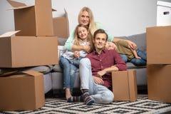 Imagen del hombre, de la mujer, de la muchacha feliz y del muchacho sentándose en el sofá gris entre las cajas de cartón para mov fotografía de archivo
