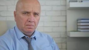 Imagen del hombre de negocios en la mala mirada interior de la oficina a la cámara que tiene una mala mirada fotografía de archivo