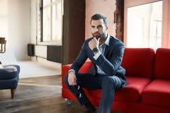 Imagen del hombre de negocios joven acertado y confiado que está mirando lejos cuidadosamente y se está sentando en oficina cómod imagen de archivo libre de regalías