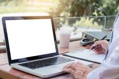Imagen del hombre de negocios que trabaja con el ordenador portátil, la tableta y d financiera Imagen de archivo