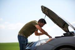Imagen del hombre joven que repara el coche roto con la capilla abierta imagen de archivo