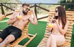 Imagen del hombre joven y de la mujer que mienten en sunbeds y mirada en uno a Llevan los bañadores y las gafas de sol Mirada de  fotos de archivo libres de regalías