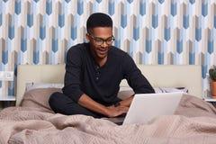 Imagen del hombre sonriente encantado que se sienta en su cama, teniendo resto, usando su dispositivo, pantalones azul marino que imagenes de archivo