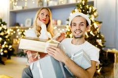 Imagen del hombre y de la mujer alegres en el casquillo de santa con el regalo en caja Foto de archivo