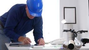 Imagen del ingeniero que tiene acceso a la información técnica usando base de datos de la tableta de tacto almacen de metraje de vídeo