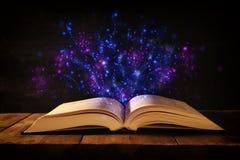imagen del libro antiguo abierto en la tabla de madera con la capa del brillo fotos de archivo libres de regalías