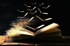 imagen del libro antiguo abierto sobre la tabla de madera con las páginas de vuelo imagen de archivo libre de regalías