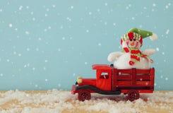 Imagen del muñeco de nieve en el coche viejo de madera del juguete sobre la tabla de madera nevosa Fotos de archivo libres de regalías