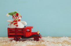 Imagen del muñeco de nieve en el coche viejo de madera del juguete sobre la tabla de madera nevosa Fotografía de archivo libre de regalías