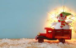 Imagen del muñeco de nieve en el coche viejo de madera del juguete sobre la tabla de madera nevosa Imagen de archivo