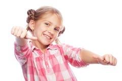 Imagen del niño feliz de la niña que se coloca sobre el fondo blanco Mirando la cámara que muestra los pulgares para arriba Fotos de archivo