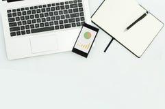 Imagen del ordenador portátil del ordenador, teléfono móvil con el gráfico, cuaderno en blanco en lugar de trabajo Fotos de archivo libres de regalías