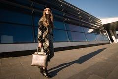 Imagen del otoño de una mujer joven en la calle Mujer en una capa y un bolso de moda foto de archivo
